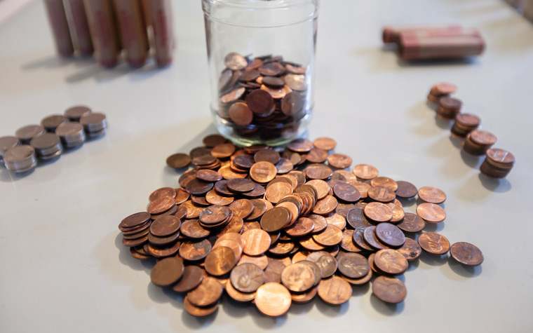 clear container with pennies and coins